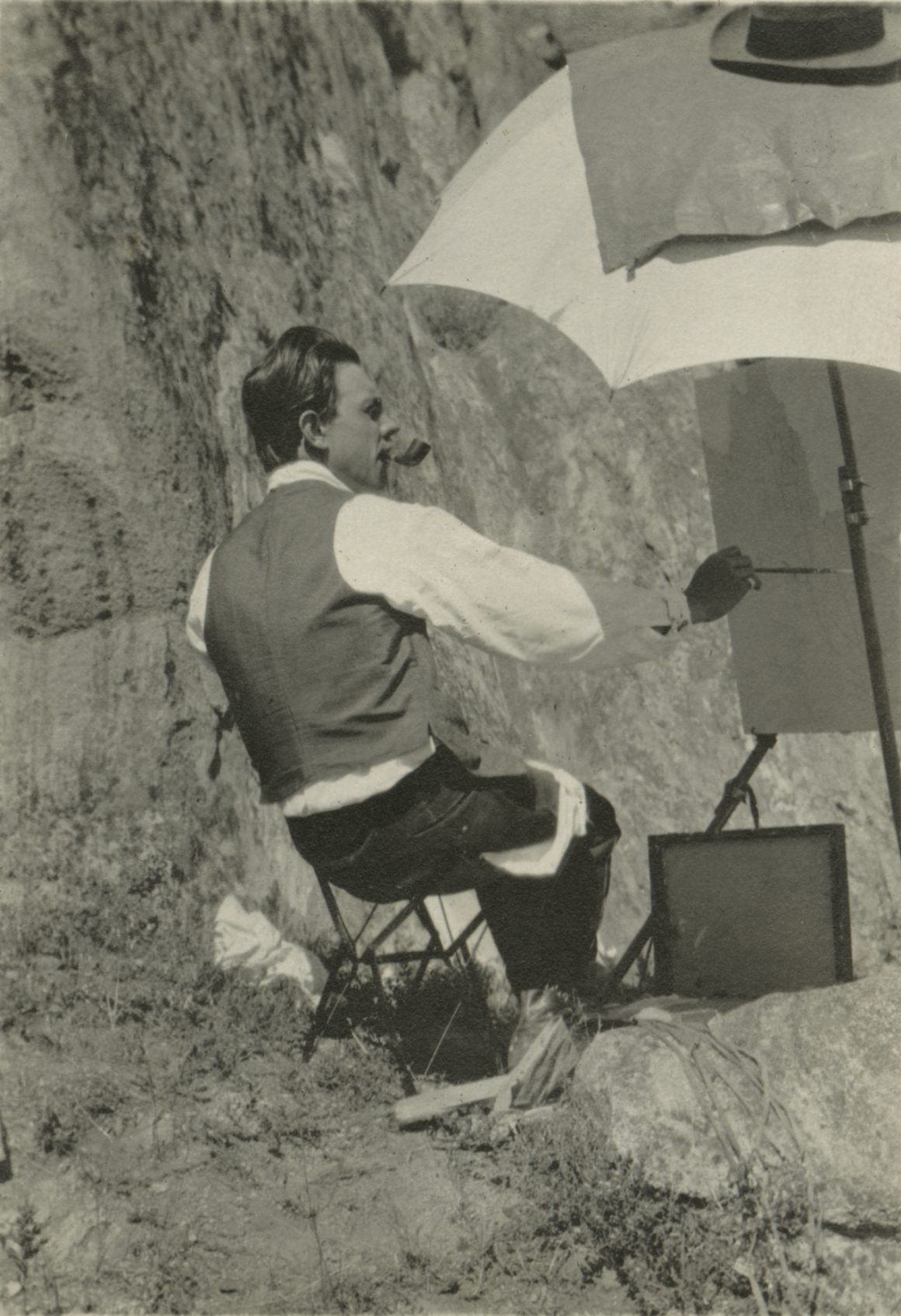 A black and white photograph of Raymond Jonson painting in Boulder Colorado, 1917