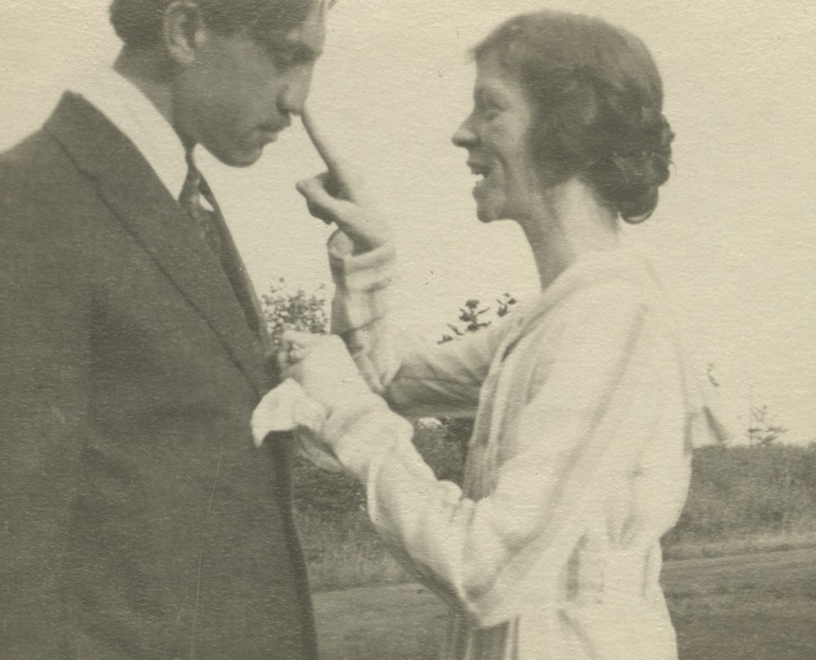 A black and white photograph of Raymond and Vera Jonson pictured outside in an unknown location in 1917. Raymond and Vera are turned facing each other while Vera presses a finger to Raymond's nose.